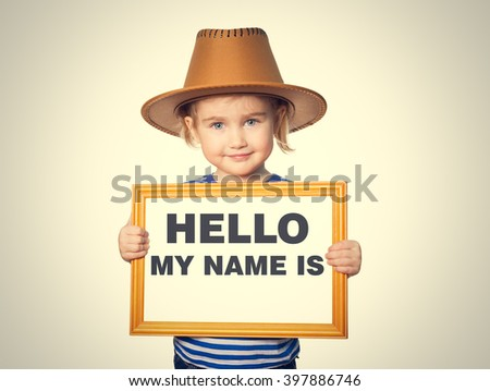 Little Funny girl in striped shirt with blackboard. Text HELLO MY NAME IS.  Isolated on gray background. - stock photo