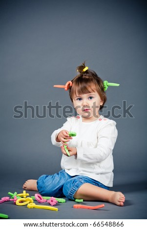 little funny girl plays with papillotes - stock photo
