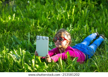 Little funny girl with a tablet makes a self-portrait (selfie) lying in the green grass. - stock photo