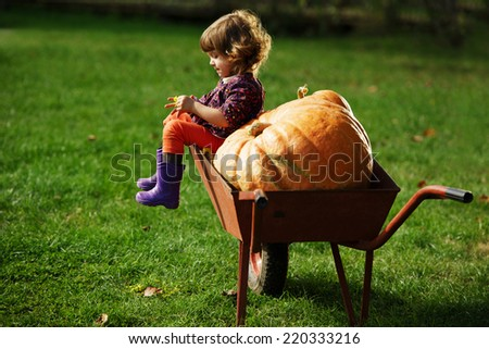 little funny girl with pumpkins in the garden - stock photo