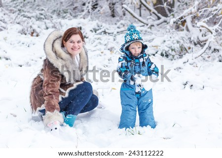 Little funny  kid boy and his mother playing with first snow in park. Happy family having fun together and enjoying winter day outdoors. On cold day, in warm clothes. - stock photo