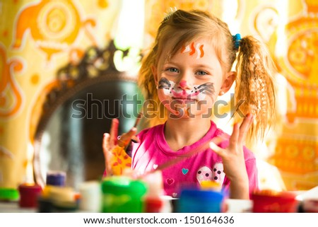 Little funny kid drawing paint with paint of face - stock photo