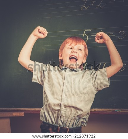 Little funny redhead schoolboy near blackboard  - stock photo