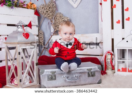Little funny toddler in a red jersey and with a tie around his neck sitting on a suitcase