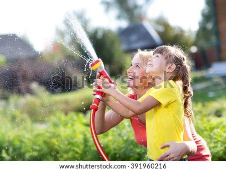 Little gardener girl with mother watering on lawn near house - stock photo