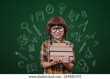 Little genius. Cheerful boy holding books and looking at camera while standing against green blackboard with sketch on it - stock photo