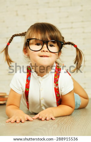 Little genius in glasses lying on the floor - stock photo