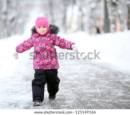little girl, a child walking in a winter park in snow - stock photo