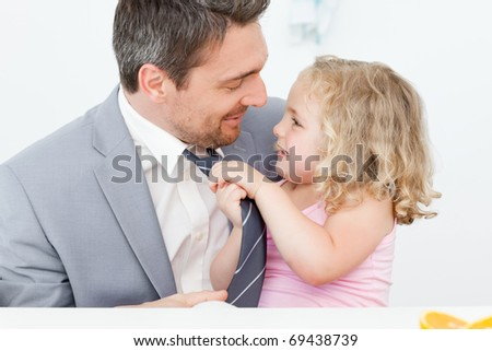 Little girl adjusting the tie of her father - stock photo