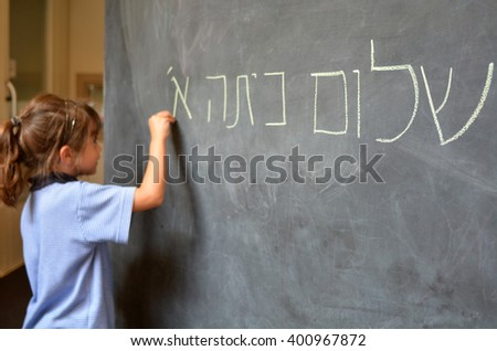 Little girl (Age 5-6) writes Hello First Grade greetings in Hebrew (Shalom Kita Alef) on a chalkboard in Israeli primary school at the beginning of the school year. Education concept photo - stock photo