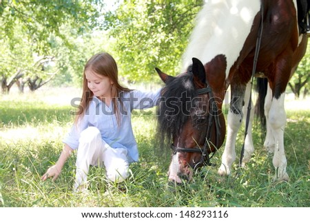 little girl and a horse - stock photo