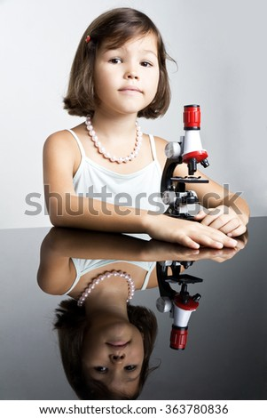 Little girl and a microscope - stock photo