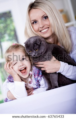 Little girl and a woman with cat in the kitchen