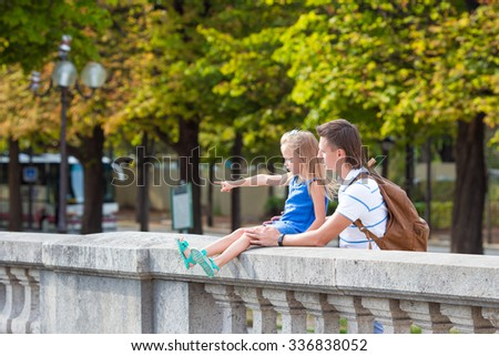 Little girl and adorable little girl in European city, Paris, France. French summer holidays, travel and people concept.
