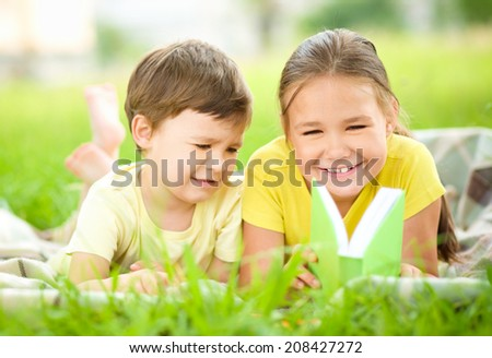 Little girl and boy are reading book while sitting on green grass - stock photo