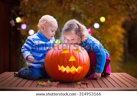 Little girl and boy carving pumpkin at Halloween. Dressed up children trick or treating. Kids trick or treat. Child in witch costume playing in autumn park. Toddler kid with jack-o-lantern.  - stock photo