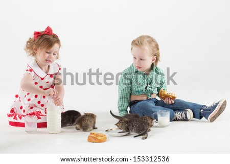 Little girl and boy drink milk, eat buns and feeds the kittens by milk - stock photo