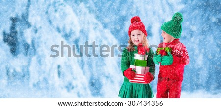 Little girl and boy in red and green knitted hat holding Christmas present boxes in winter park on Xmas eve. Kids play outdoor in snowy winter forest. Children opening presents. Panorama size banner - stock photo