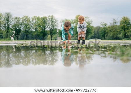 Little girl and boy looking at the puddle. Brother and sister in the park outdoors