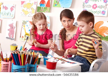 Little girl and boy  painting with teacher in school. - stock photo