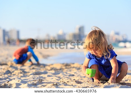 little girl and boy play with sand on sunset beach - stock photo
