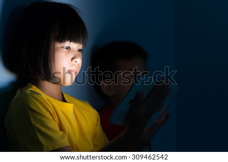 Little girl and boy playing tablet pc in bedroom at night - stock photo