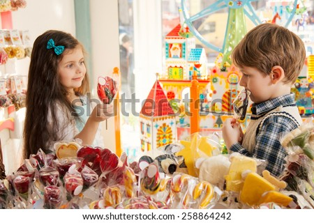 Little girl and boy showing candy to each other - stock photo