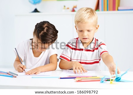 Little girl and boy studying together