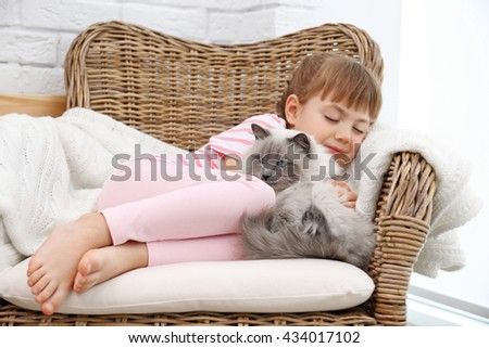 Little girl and cat on wicker armchair in living room - stock photo