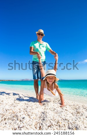 Little girl and dad having fun on white beach - stock photo