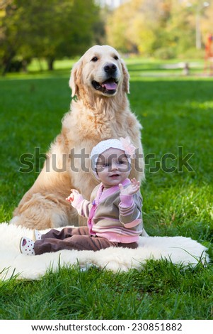 Little girl and dog of breed a golden retriever sit on a green grass - stock photo