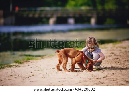 Little girl and dog on the beach in sunny summer day. Child with puppy outdoors.