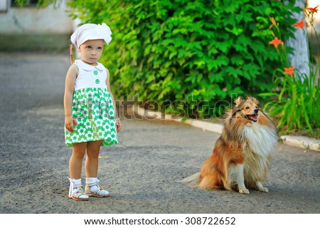 Little girl and dog sheltie walk in the park. The girl was offended. - stock photo