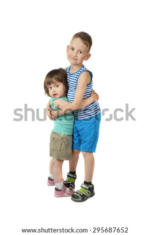 Little girl and elder boy stand embracing isolated on white background with shadow - stock photo