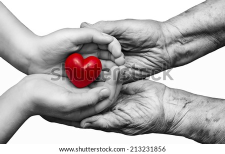 Little girl and elderly woman keeping red heart in their palms together, isolated on white background, symbol of care and love - stock photo