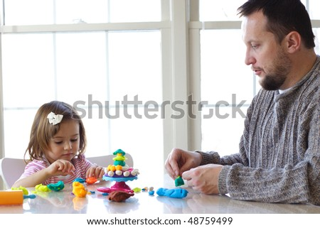Little girl and father creating toys from play dough - stock photo