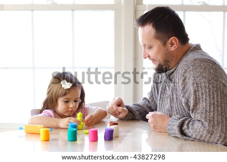 Little girl and father creating toys from playdough - stock photo