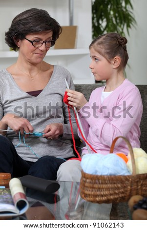 little girl and grandmother knitting together - stock photo