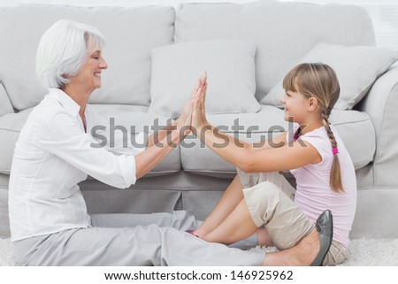 Little girl and grandmother playing together while they are sat on a carpet in the living room - stock photo
