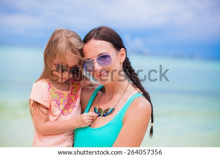 Little girl and happy mom during summer beach vacation - stock photo
