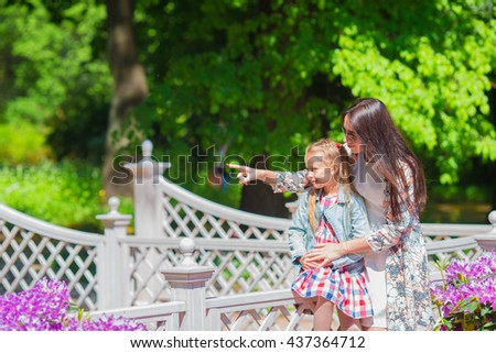 Little girl and happy mother enjoying warm day in bloomig tulip garden - stock photo
