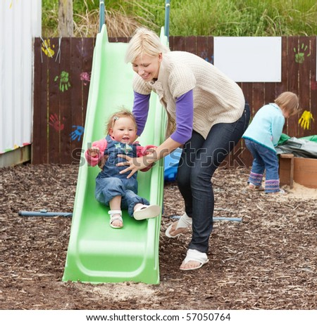Little girl and her beautiful mother having fun with a chute at the playground - stock photo