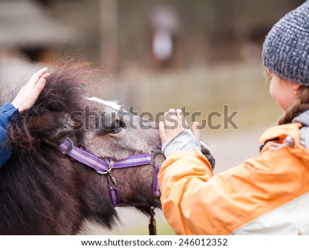 Little girl and her best friend pony - stock photo