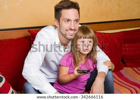 Little girl and her brother enjoy eating popcorn and watching tv at home - stock photo