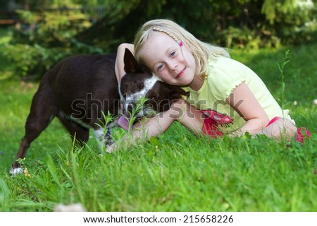 Little Girl and her Dog Little girl hugging her dog who does not look too impressed. - stock photo