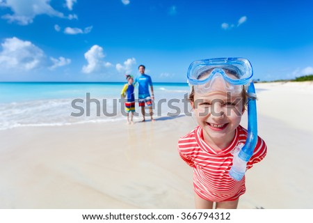 Little girl and her family with snorkeling equipment enjoying beach vacation - stock photo