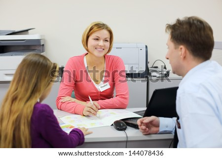 Little girl and her father sit in office and talk with realtor. Focus on woman. - stock photo