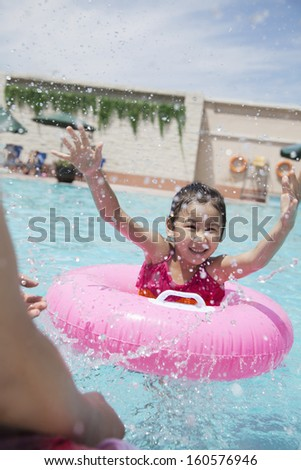 Little girl and her father splashing in pool - stock photo