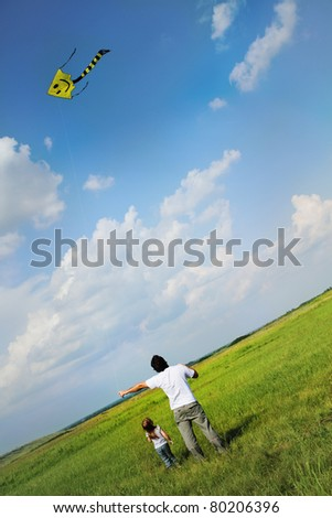 Little girl and her father with flying a kite in the summer field - stock photo