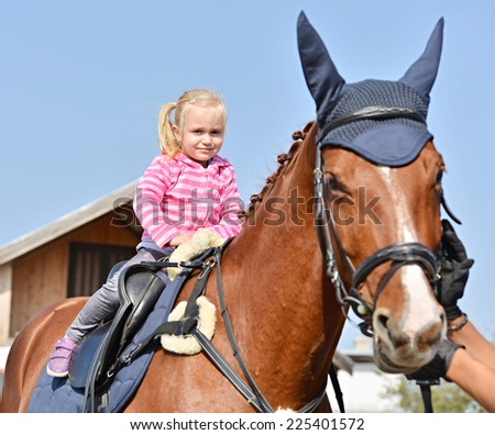 little girl and her horse - stock photo